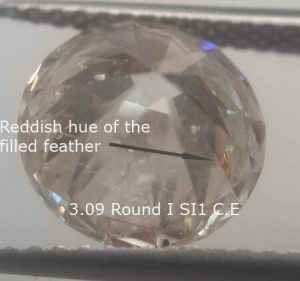 Clarity enhancement red hue of the filler, bottom in a round diamond